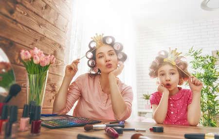 madre e hija: amante de la familia feliz. La madre y la hija están haciendo para el cabello, manicura, haciendo su maquillaje y divirtiéndose. La madre y la hija se sienta en el tocador en la casa. Foto de archivo
