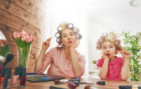 daughter mother: Happy loving family. Mother and daughter are doing hair, manicures, doing your makeup and having fun. Mother and daughter sitting at dressing table at house. Stock Photo