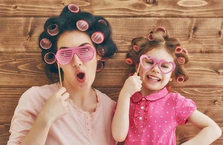 Funny familie! Moeder en haar kind dochter meisje met een papieren accessoires. Beauty grappig meisje houden papieren bril op stok. Mooie jonge vrouw bedrijf papier bril op stok. Stockfoto