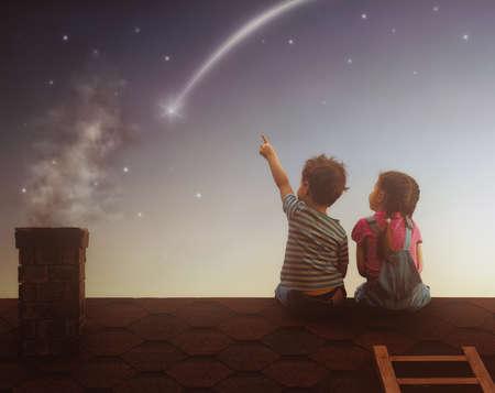 Duas crianças bonitos sentar-se no telhado e olhar para as estrelas. Menino e menina faz um desejo ao ver uma estrela cadente.