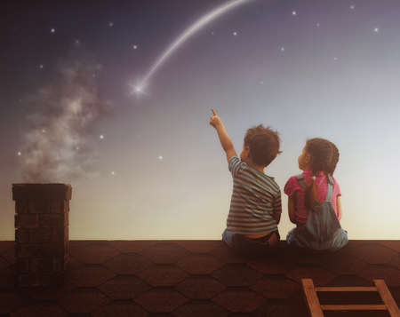 Two cute children sit on the roof and look at the stars. Boy and girl make a wish by seeing a shooting star. Stock Photo