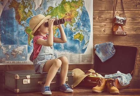 fin de semana: bebé feliz preparándose para el viaje. Chica empaca sus maletas y jugando con los prismáticos.