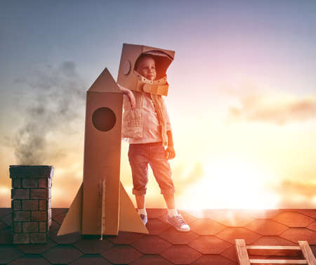 Little child boy plays astronaut. Child on the background of sunset sky. Child boy in an astronaut costume standing on the roof of the house and looking at the sky and dreaming of becoming a spaceman. 스톡 콘텐츠