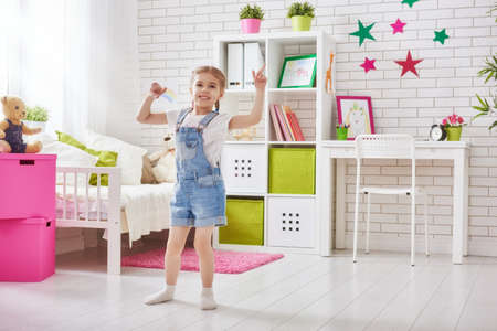 game room: funny child girl plays at home. girl having fun and dancing. recreation and entertainment at home.