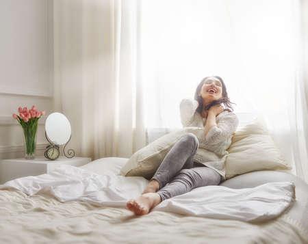 ベッドの上の日当たりの良い朝を楽しんで幸せな若い女 写真素材