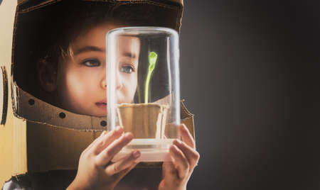 protection concept: Child is dressed in an astronaut costume. Child sees a sprout in a glass case. The concept of environmental protection.
