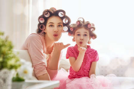 Happy loving family. Mother and daughter are doing hair and having fun. Mother and her child girl playing, kissing and hugging. Banque d'images