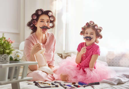 Funny family! Mother and her child daughter girl with a paper accessories. Mother and daughter preparing for a party and having fun. Beautiful young woman and funny girl with a paper mustache on stick.
