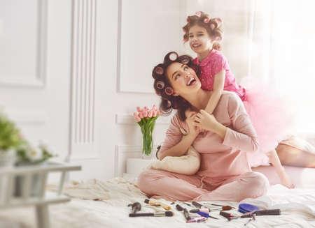 família amorosa feliz. Mãe e filha estão fazendo o cabelo e se divertindo. Matriz e sua menina que joga e que abraça.