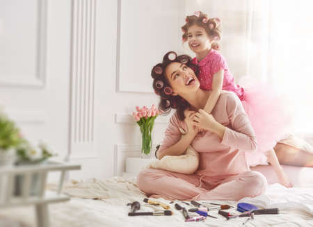 kisses: Happy loving family. Mother and daughter are doing hair and having fun. Mother and her child girl playing and hugging.