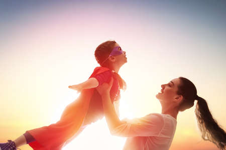 母と彼女の子供の女の子一緒に遊んで。スーパー ヒーローの衣装の女の子。 写真素材