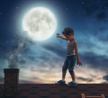 pipe dream: Child boy walks on the roof in the moonlight.