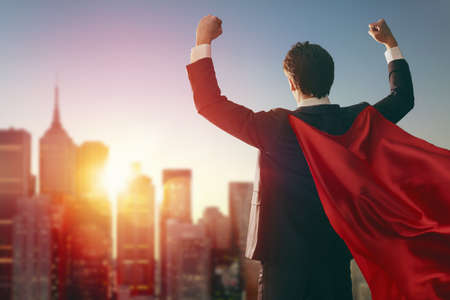 superhero businessman looking at city skyline at sunset. the concept of success, leadership and victory in business. Stockfoto
