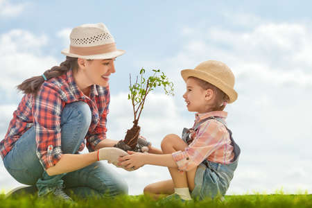 Mom and her child girl plant sapling tree. Spring concept, nature and care. Stock Photo