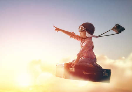 Dreams of travel! Child flying on a suitcase against the backdrop of a sunset. Stock Photo