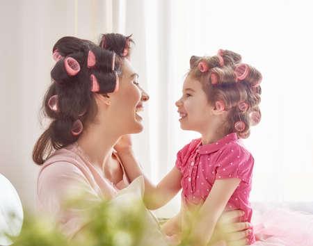 madre e hija: amante de la familia feliz. La madre y la hija están haciendo el pelo y divertirse. La madre y su niña de juego infantil y abrazos.