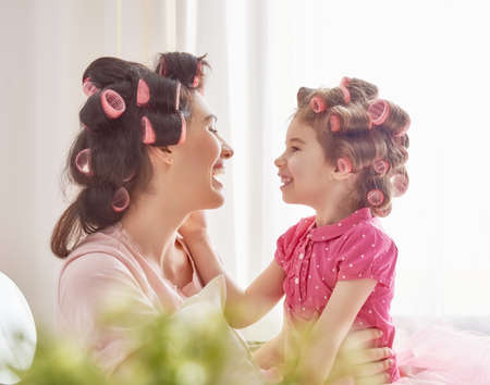 mom and daughter: Happy loving family. Mother and daughter are doing hair and having fun. Mother and her child girl playing and hugging.