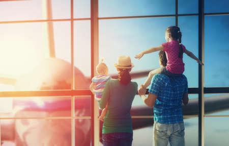 Gelukkige familie met kinderen op de luchthaven. Ouders en hun kinderen kijken uit het raam naar het vliegtuig.