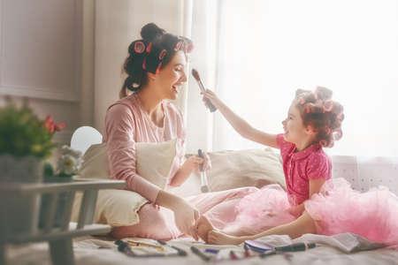 幸せな愛情のある家族。母と娘は髪を行うと楽しい時を過します。母と娘の寝室のベッドの上に座ってお化粧を行います。 写真素材