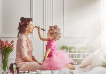 CHILD CARE: Happy loving family. Mother and daughter are doing hair and having fun. Mother and daughter doing your makeup sitting on the bed in the bedroom. Stock Photo