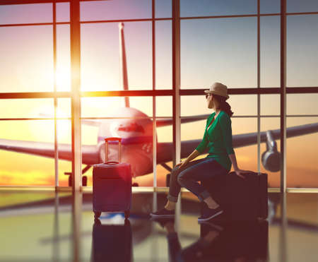 air plane: Young beautiful woman looks at a plane at the airport.