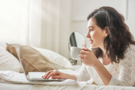 mujer en la cama: hermosa mujer casual feliz que trabaja en un ordenador portátil sentado en la cama en la casa.