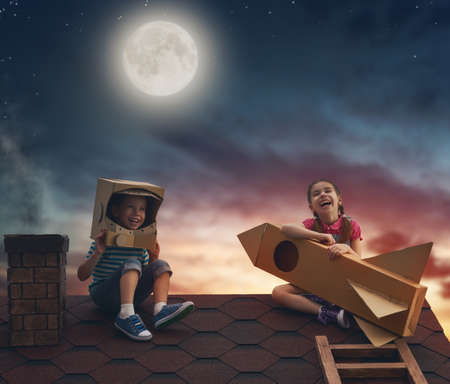 Two little children playing astronauts. Children on the background of moon sky. Child boy in an astronaut costume and child girl with toy rocket standing on the roof of the house and looking at the sky and dreaming of becoming a spacemen. Banque d'images