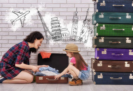 packing suitcase: happy family preparing to vacation. mother and her child daughter packing their bags. Stock Photo