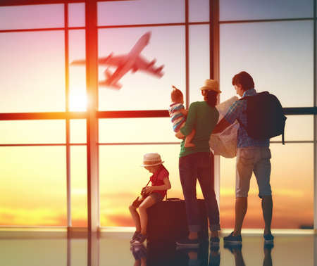 familia: Familia feliz con las maletas en el aeropuerto.