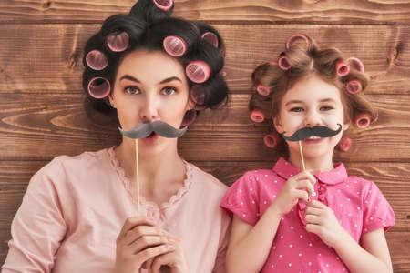 dois: Família engraçada! Matriz e sua menina criança filha com acessórios de papel. Beleza menina engraçada segurando bigode papel na vara. Bela jovem segurando bigode papel na vara.
