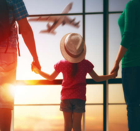 Happy family with child at the airport. Parents and child girl look out the window at the airplane. Archivio Fotografico