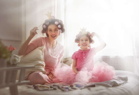 Funny family! Mother and her child daughter girl with a paper accessories. Mother and daughter preparing for a party and having fun. Beautiful young woman and funny girl with a paper crowns on sticks. Stock Photo