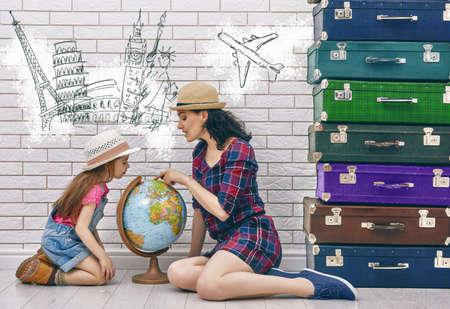 cestovní: šťastná rodina připravuje na cestu. Matka a dcera při pohledu na celém světě a vybrat si zemi cestovat.