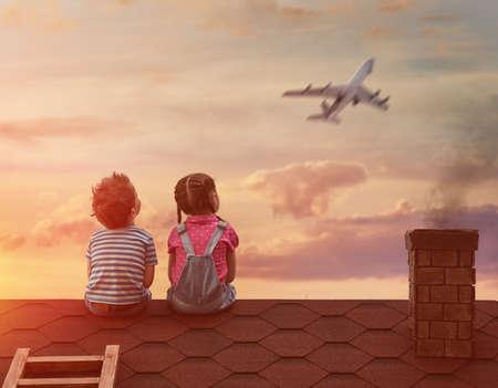 Twee kleine kinderen spelen op het dak van het huis en kijken naar de hemel en dromen ervan om een piloten. Stockfoto