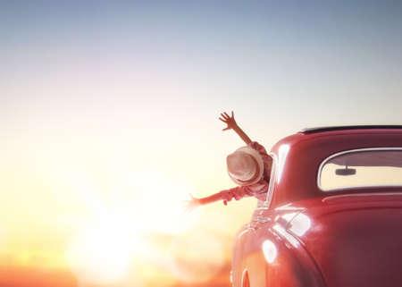 Toward aventura! Menina que relaxa e que aprecia viagem. A menina feliz anda no por do sol no carro vintage.