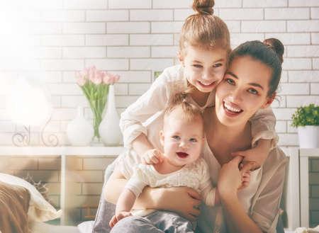 Lycklig kärleksfull familj. Mor och hennes döttrar barn tjejer som spelar och kramas. Stockfoto