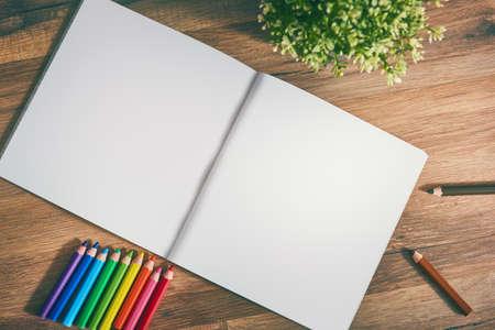autocuidado: cuaderno de dibujo y lápices de colores sobre una mesa de madera.