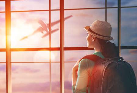 Mulher bonita nova olha para um avião no aeroporto. Imagens