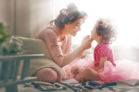 putting lipstick: Happy loving family. Mother and daughter are doing hair and having fun. Mother putting lipstick on her daughter.