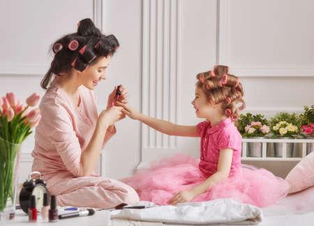 amante de la familia feliz. La madre y la hija están haciendo para el cabello, manicura y divirtiéndose. Madre e hija sentada en la cama en el dormitorio.