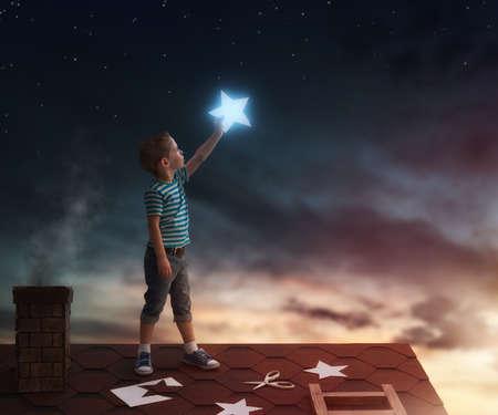 Conto de fadas! A criança pendurando as estrelas no céu. Menino no telhado corta estrelas. Imagens