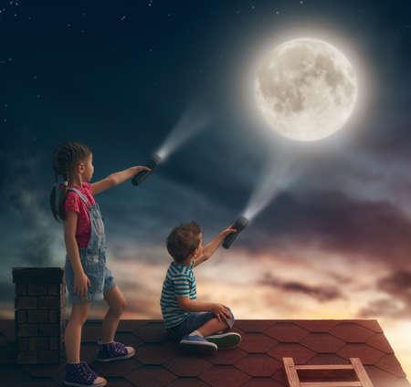 Dos niños lindos que se sientan en el techo y miran a la luna.