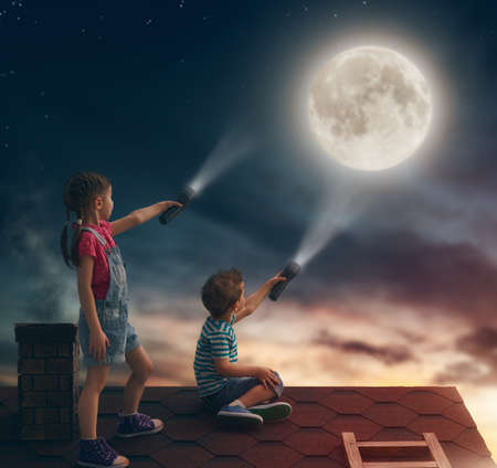 flashlight: Two cute children sit on the roof and look at the moon. Stock Photo