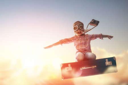 case: Dreams of travel! Child flying on a suitcase against the backdrop of a sunset. Stock Photo