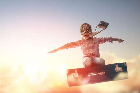 valise voyage: Rêves de Voyage! Enfant volant sur une valise en toile de fond un coucher de soleil. Banque d'images