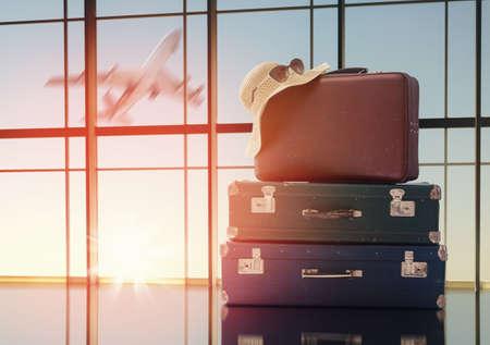 여행과 휴가의 개념. 창문과 석양에 대한 여행 가방