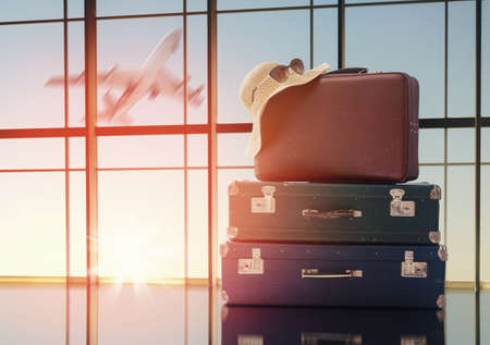 the concept of travel and holiday. suitcases against the window and the sunsets Stock Photo