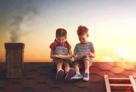 I bambini la lettura di un libro seduto sul tetto della casa. Lettura del ragazzo e ragazza dalla luce del tramonto. Archivio Fotografico
