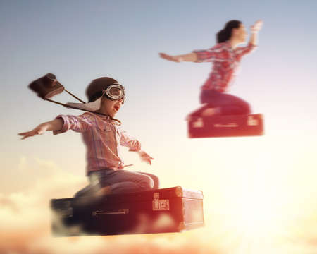 pretending: Dreams of travel! Child girl and her mom flying on a suitcase against the backdrop of a sunset.