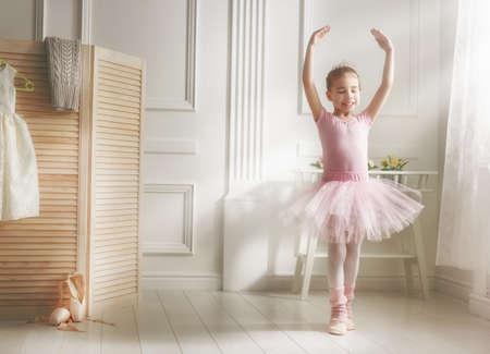 Cute dziewczynka marzy o zostaniu baletnicą. Dziewczynka dziecka w różowe tutu taniec w pomieszczeniu. Dziewczynka uczy się baletu.